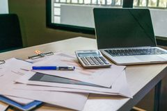 Niezorganizowany upaćkany biurko z laptopem, kalkulatorem i dokumentami przy miejsce pracy, obraz stock