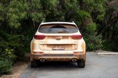 Niezwykle brudny Kia Sportage SUV samochód parkujący blisko krzaka po przygody fotografia stock