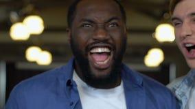 Niezwykle szczęśliwi multiracial mężczyźni świętuje ulubionego sport drużyny cel, relaksują zdjęcie wideo