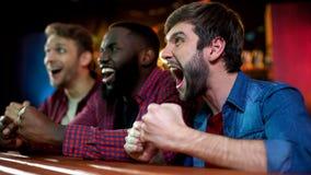 Niezwykle szczęśliwi multiracial przyjaciele świętuje zwycięstwo krajowy bokser w barze zdjęcia stock