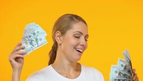 Niezwykle uradowana kobieta pokazuje wiązki dolary na kamerze, loteryjny zwycięzca zbiory