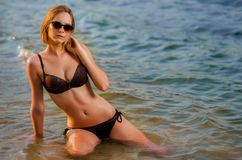 Nifty caucasian young woman in a glasses on the beach. Is sitting on azure water. Recreation and pampering on the seashore ocean, river, lake in sunset light stock images