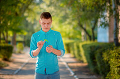 Nifty teenager holds one finger modern gadget fidget spinner. Man on the azure shirt and blue jeans playing with green spinner outdoors on the bright floral stock photography