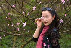 A nifty woman and Peach Flower. A nifty woman was putting a peach flower near her eye and looking to me Royalty Free Stock Images