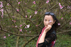 A nifty woman and Peach Flower. A nifty woman was putting a peach flower near her eye and looking to me royalty free stock photo