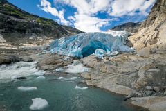 Nigardsbreen Glacier ice and lake landscape. Wide angle view of Nigardsbreen Glacier ice, blue cave and melted water lake. Popular Norway landmark and national royalty free stock photography