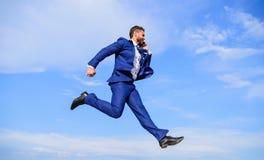 Nigdy zatrzymuje Biznesmena kostiumu formalny skok podczas gdy wywoławczy smartphone nieba tło Biznesmen rozwiązuje biznesowych p zdjęcia stock