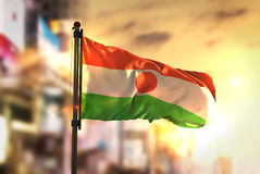 Niger Flag Against City Blurred Background At Sunrise Backlight Royalty Free Stock Photography