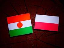 Niger flag with Polish flag on a tree stump isolated. Niger flag with Polish flag on a tree stump royalty free illustration