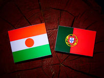 Niger flag with Portuguese flag on a tree stump isolated. Niger flag with Portuguese flag on a tree stump vector illustration