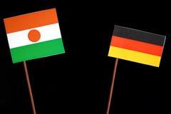 Niger flaga z niemiec flaga na czerni obraz stock