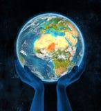 Niger op aarde in handen Stock Fotografie