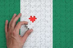 Nigeria flag is depicted on a puzzle, which the man`s hand completes to fold.  royalty free illustration