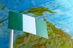 Nigeria flag with a globe map as a background royalty free stock image