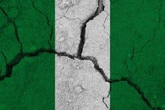 Nigeria-Flagge auf der gebrochenen Erde stockbild