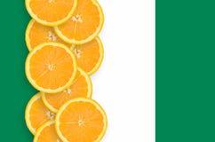 Nigeria-Flagge und vertikale Reihe der Zitrusfruchtscheiben stockbilder