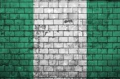 Nigeria-Flagge wird auf eine alte Backsteinmauer gemalt stockfotografie