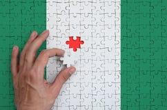 Nigeria-Flagge wird auf einem Puzzlespiel dargestellt, das die Mann ` s Hand abschließt, um zu falten stockbild