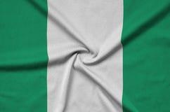 Nigeria-Flagge wird auf einem Sportstoffgewebe mit vielen Falten dargestellt Sportteamfahne lizenzfreie stockfotografie