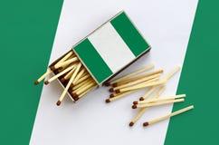 Nigeria-Flagge wird auf einer offenen Streichholzschachtel gezeigt, von der einiges Match und Lügen auf einer großen Flagge fällt lizenzfreie stockfotos