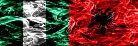 Nigeria, Nigeryjski vs Albania, albańczyka dymu flaga umieszczająca strona strona - obok - Gęsty abstrakt barwił silky dymne flag royalty ilustracja