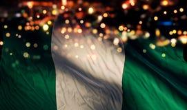Nigeria-Staatsflagge-Licht-Nacht-Bokeh-Zusammenfassungs-Hintergrund lizenzfreies stockbild
