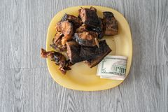 Nigerian dried roasted fish with Naira notes. To buy it stock photography