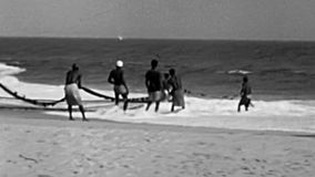 Nigerian fishermen fishing on the beach. Lagos, Nigeria, Africa - Circa 1977: Black fishermen fishing with a fish net on the beach on Guinea Gulf in Lagos City stock video