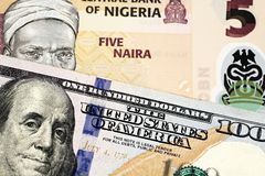 A Nigerian Five Naira Note With An American One Hundred Dollar Bill. A macro image of a peach colored Nigerian five Naira bill with an American one hundred stock photography