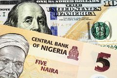 A Nigerian Five Naira Note With An American One Hundred Dollar Bill. A macro image of a peach colored Nigerian five Naira bill with an American one hundred stock image