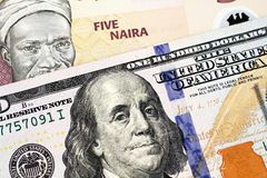 A Nigerian Five Naira Note With An American One Hundred Dollar Bill. A macro image of a peach colored Nigerian five Naira bill with an American one hundred stock photos