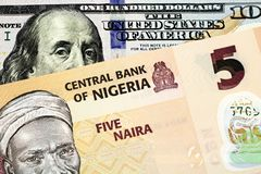 A Nigerian Five Naira Note With An American One Hundred Dollar Bill. A macro image of a peach colored Nigerian five Naira bill with an American one hundred royalty free stock image