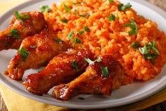 Nigerian food: spicy Jollof rice with fried chicken closeup. horizontal. Nigerian food: spicy Jollof rice with fried chicken closeup on a plate. horizontal stock photo