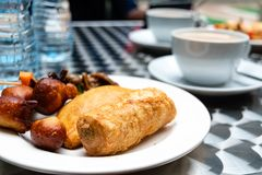 Nigerian meat pie, puff-puff, fish roll and stick meat gizzard pastries or Nigerian small chops in white saucer for Nigerian break stock images