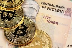 Nigerian 5 Naira bank notes with gold bitcoins Royalty Free Stock Photography