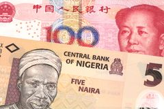 A Nigerian naira bill with with a Chinese yuan bank note close up. An orange five naira note from Nigeria with a red, one hundred yuan renminbi note from China stock images