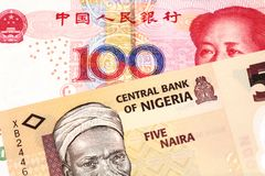 A Nigerian naira bill with with a Chinese yuan bank note close up. An orange five naira note from Nigeria with a red, one hundred yuan renminbi note from China royalty free stock images