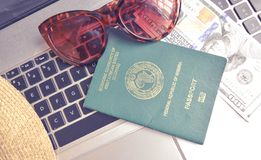 Nigerian Passport with US Dollar on keyboard of laptop with sunglasses royalty free stock photos