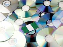 Nigeryjska flaga na górze cd i DVD stosu odizolowywającego na bielu Fotografia Stock