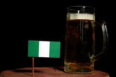 Nigeryjska flaga z piwnym kubkiem na czerni Obrazy Stock