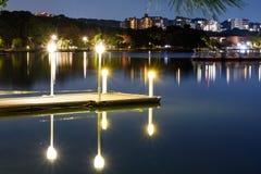 Nigh landskap av ljus på pir eller skeppsdockan med mycket slät vatten- och byggnadsreflexion arkivbild