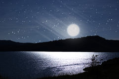 Dark night with full moon. Reflexed in lake water Royalty Free Stock Photos