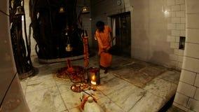 Night Aarti in hindu temple Someshwar Mahadev Rishikesh monk waves with fan near religious atributes
