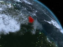 French Guiana at night from orbit. Night above French Guiana highlighted in red on model of planet Earth in space. 3D illustration. Elements of this image Royalty Free Stock Photo