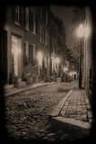 Night on Acorn Street. Sepia toned image of an old 19th Century cobble stone road in Boston Massachusetts, lit only by the gas lamps revealing the shuttered royalty free stock photography