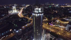 Night aerial flight over center of Moscow. House of music hall. Modern Glass buildings. Night road traffic. Close approach. UAV quadcopter drone 4K footage stock video