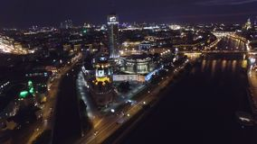 Night aerial flight over center of Moscow. House of music hall. Modern Glass buildings. Night road traffic. Close approach. UAV quadcopter drone 4K footage stock footage