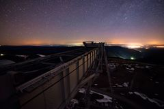 Night aerial view from construction crane to observatory on background of starry sky and Caucasian mountains.  Stock Photo