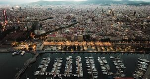 Night aerial view from drones of old port in Barcelona with of sailboats and yachts and gothic quarter, historical part