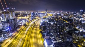 Night aerial view of tel aviv skyline with urban skyscrapers and Long exposure car tail lights Royalty Free Stock Images